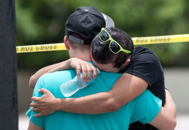 Supported by a friend, a man weeps for victims of the mass shooting just a block from the scene in Orlando.